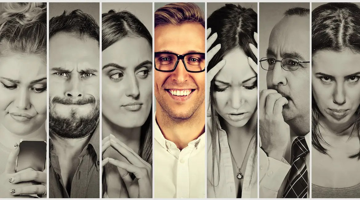An image shows a 7 people in individual frames. The man in the middle is smiling while the other 6 people have unpleasant looks on their face. This picture serves as the featured image for Balanced Achievement's article on how the individuals you find difficult to deal with are your greatest teachers.