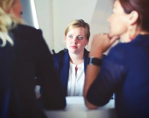 A woman is shown with a perplexed look on her face as she attentively watches two other women sitting at the same table as her having a conversation.