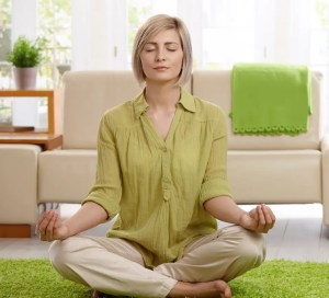An image shows a woman sitting on floor at home doing yoga meditation. This image represents the idea that there are strategies and practices we can utilize to fully learn from our greatest teachers.