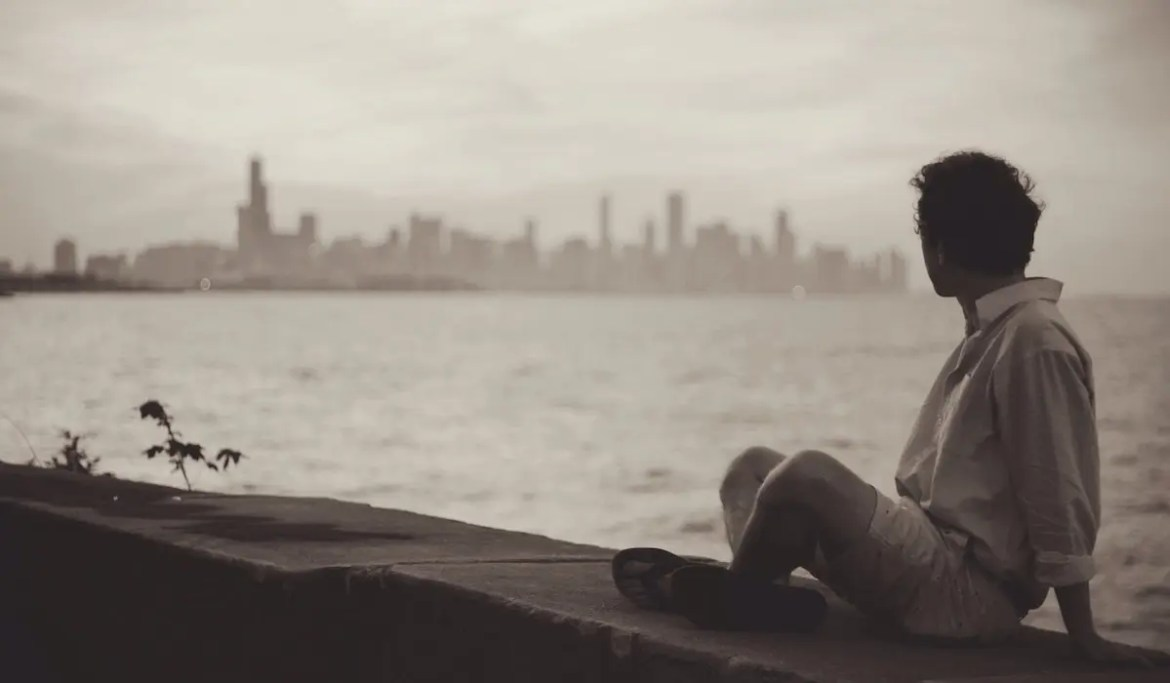 A black and white image shows a young man sitting on the ledge near the ocean as he looks across the water at New York City. This picture serves as the featured image for Balanced Achievement's article on the conscious question of 'What do I want in life?'