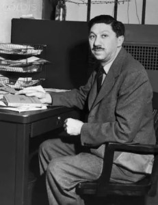 An image shows Abraham Maslow sitting at his desk with a variety of papers and books scattered on the desk's surface. This photo is courtesy of the Corbis Corporation.