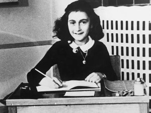 An image shows a young Anne Frank smiling as she sits at a desk with a pen in hand writing.