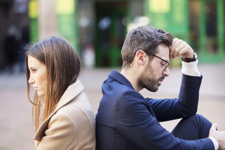 An image shows a couple sitting on the ground back to back with neither the man or woman looking very happy. This picture serves as the featured image for Balanced Achievement's article on Empathically changing your behavior to promote change in others.