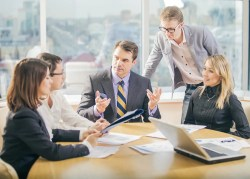 An image shows 5 business people working together in meeting room. The boss in the picture has his hands raised and looks like he is asking questions of his employees.