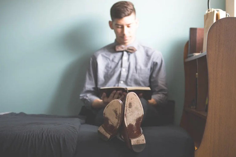 An image shows a young man dressed in nice clothes and a bowtie as he sits on his bed reading a book. This picture serves as the featured image for Balanced Achievement's article on how the personal characteristic of humility is vital for sustaining meaningful success.