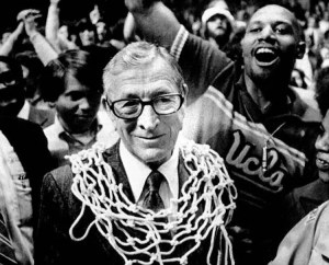 An image shows legendary basketball coach John Wooden, with a basketball net around his neck, after winning one of his 10 national titles. Wooden is a perfect example of an individual who's achieved great things with humility.