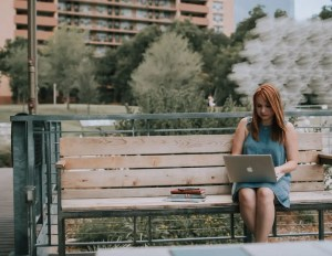 An image shows a girl sitting on a bench working on her computer with a stack of books by her side. This image represents the idea that humility means working hard, paying close attention to detail and going the extra mile.
