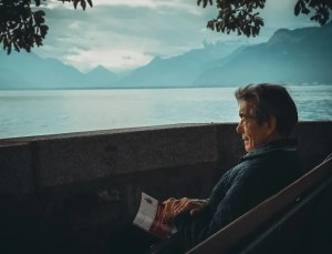 An image shows an older man, with a book in hand, sitting on a bench that overlooks the ocean and mountains. Thanks to his humility, he's continued to grow and find success throughout his life.