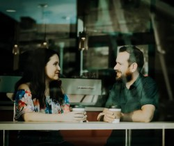 An image shows a man and woman having a great conversation in a coffee shop. This image represents the idea that empathetic understanding is a powerful communication tool.