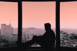 An image shows the silhouette of a man as he sits on the edge of window in a high-rise building that overlooks a city. This image represents the idea that our schemas about life play an influential role on our happiness.