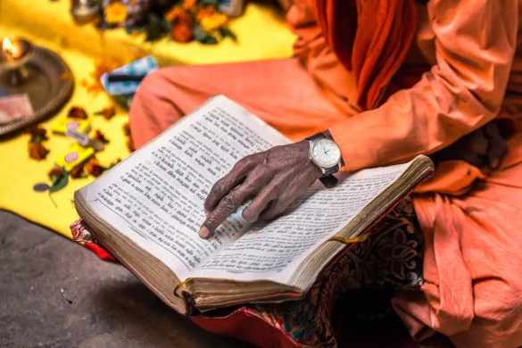 An image shows an old sadhu pointing along as he reads out of a holy Hindu book, such as the Upanishads, in Varanasi, India. This picture serves as the featured image for Balanced Achievement's 'Quote 20: Wisdom from the Upanishads' article.