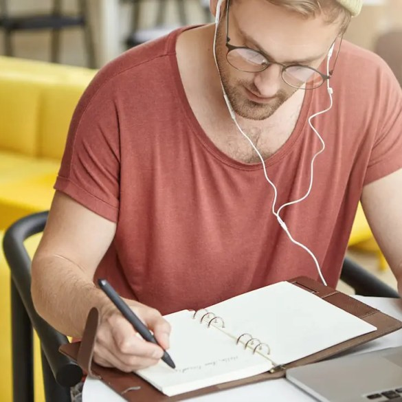 An image shows a young man writing with headphones in his ears as he's writing in his journal. This pictures serves as the featured image for Balanced Achievement's article on the 5 best personal development podcasts.