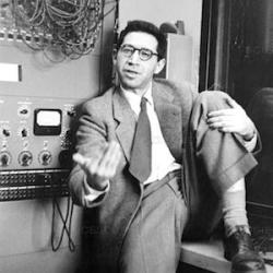 An image shows psychologist Leon Festinger sitting in front of an electronic machine while expressively talking with his hands. Festinger's theory of cognitive dissonance played an important role in the cognitive revolution.