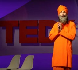 An image shows yogic monk Dada Gunamuktananda onstage giving a TED Talk with a TED logo in the background. Gunamuktananda's speech titled Consciousness - The Final Frontier is one of the best TED Talks on mindfulness and meditation.