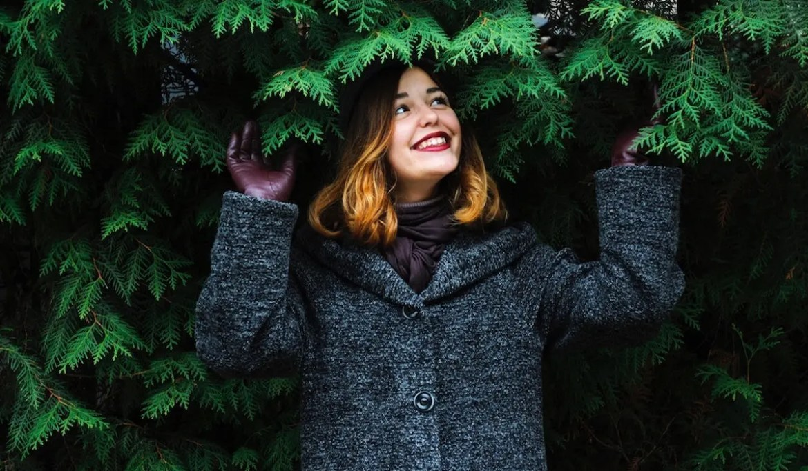 An image shows a young woman standing underneath a pine tree as she looks up at the leafs with a big smile on her face. This picture serves as the featured image for Balanced Achievement's article titled 'Life's Ultimate Aim Is To Find Enjoyment In The Days'.