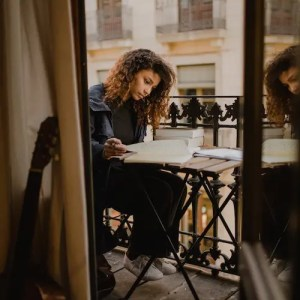 An image shows a young woman sitting on the patio of an apartment writing in a notebook with a pile of books next to her. This image represents the idea that becoming a student of life can help us achieve life's ultimate of graciously enjoying each day.
