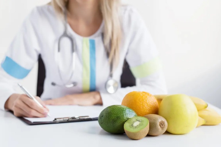 An image shows an assortment of fruit in the foreground with a doctor writing on a notepad in the background. This picture serves as the featured image for Balanced Achievement's article on The Mayo Clinic Diet