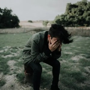 An image shows a young man sitting out in a field with his hands covering his face in what appears to be frustration. This picture represents the idea of how our most basic psychological and conditioned drives leave us unsatisfied in Balanced Achievement's article on life's ultimate aim.