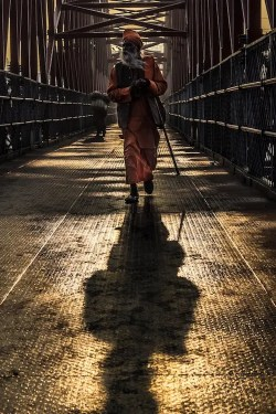 An image shows a Hindu sadhu walking on a bring with his shadow on the ground in front of him. This picture is used in Balanced Achievement's article on consciousness quotes.