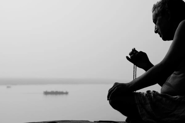 An image shows a Hindu man sitting in a meditative posture with the Ganges River in the background. This picture serves as the featured image for Balanced Achievement's article titled 20 Consciousness Quotes That Illuminate Your True Spiritual Nature.