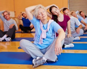 An image shows an older lady and other individuals gently stretching their necks while sitting on yoga mats. This image represents the many practices used in Mindfulness-Based Stress Reduction (MBSR).