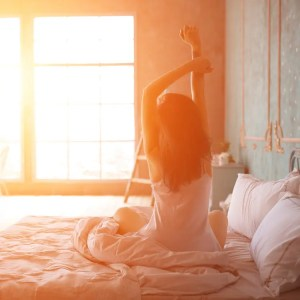 An image shows a woman stretching after waking up as the sun shines brightly through her windows. This image is featured in Balanced Achievement's article on morning questions