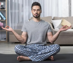 An image shows a young man practicing meditation in his home. this image is featured in Balanced Achievement's article titled 'The Yin and Yang of Stillness and Flow'.