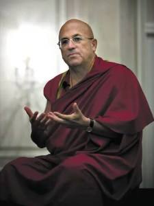 An image shows Buddhist monk Matthieu Richard sitting on a chair talking expressively with his hands.