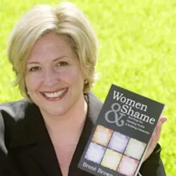 An image show Brene Brown holding her first book 'Women & Shame.'