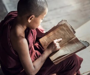 An image shows a young Buddhist novice monk reading old scriptures in his monastery. This picture is featured in Balanced Achievement's article on 20 authentic Buddha quotes from the Dhammapada.