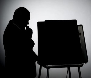 An image shows the silhouette of a man in thought as he stands at a voting ballot box. This image represents the idea that politicians use the psychology of political campaign advertising to sway voters.