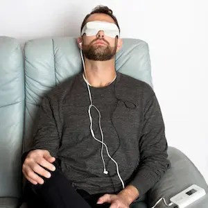 An image shows a man using the Kaisan DeepVision device which is featured in Balanced Achievement's article on meditation tools of the digital age.