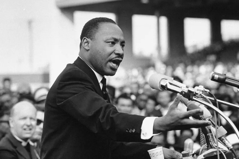 An image shows Martin Luther King Jr. passionately speaking into 5 to 10 microphones as a big audience looks on in the background. This image is used as the featured image of Balanced Achievement's article looking at 20 Martin Luther King Jr. quotes.