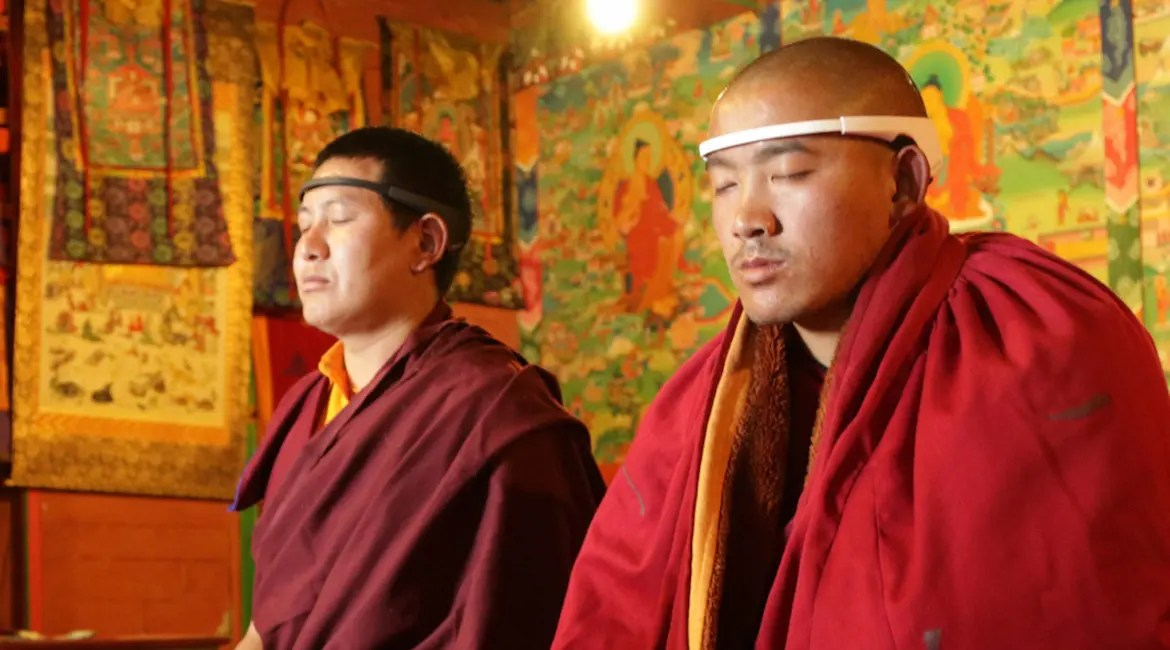 An image shows two Buddhist monks practicing meditation while wearing the Muse brain sensing headband. This pictures serves as the featured image of Balanced Achievement's article looking at meditation tools of the digital age.