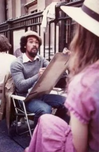 An image shows the great spiritual teacher Mooji painting a portrait of a woman on the streets of London.