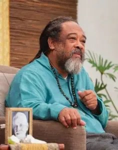 An image shows the great spiritual teacher Mooji at a Satsang spiritual talk with a picture of Ramana Maharshi by his side.
