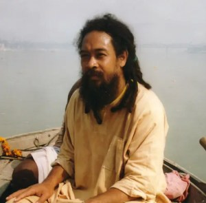 An image shows the great spiritual teacher Mooji on his first visit to India, which took place when he was younger. In the photo he's sitting in a boat on the sacred Ganges River.