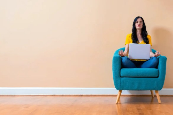 A photo is shown of a woman sitting in meditation position on a chair with her computer in her lap. The picture serves as the featured image for Balanced Achievement's article looking at free Coronavirus Meditation Resources.