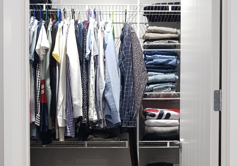 men's clothes hanging in wardrobe