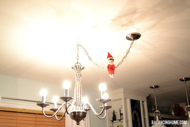 Elf On The Shelf Swinging From A Chandelier