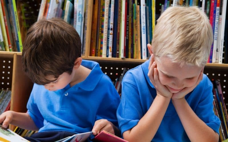 two boys reading in library