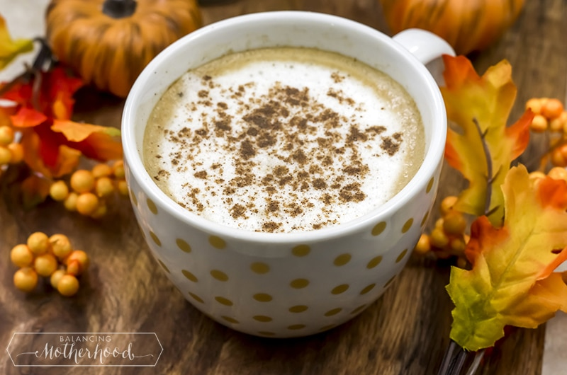 Mug of paleo pumpkin latte in a polka dot mug surrounded by fall colored leaves