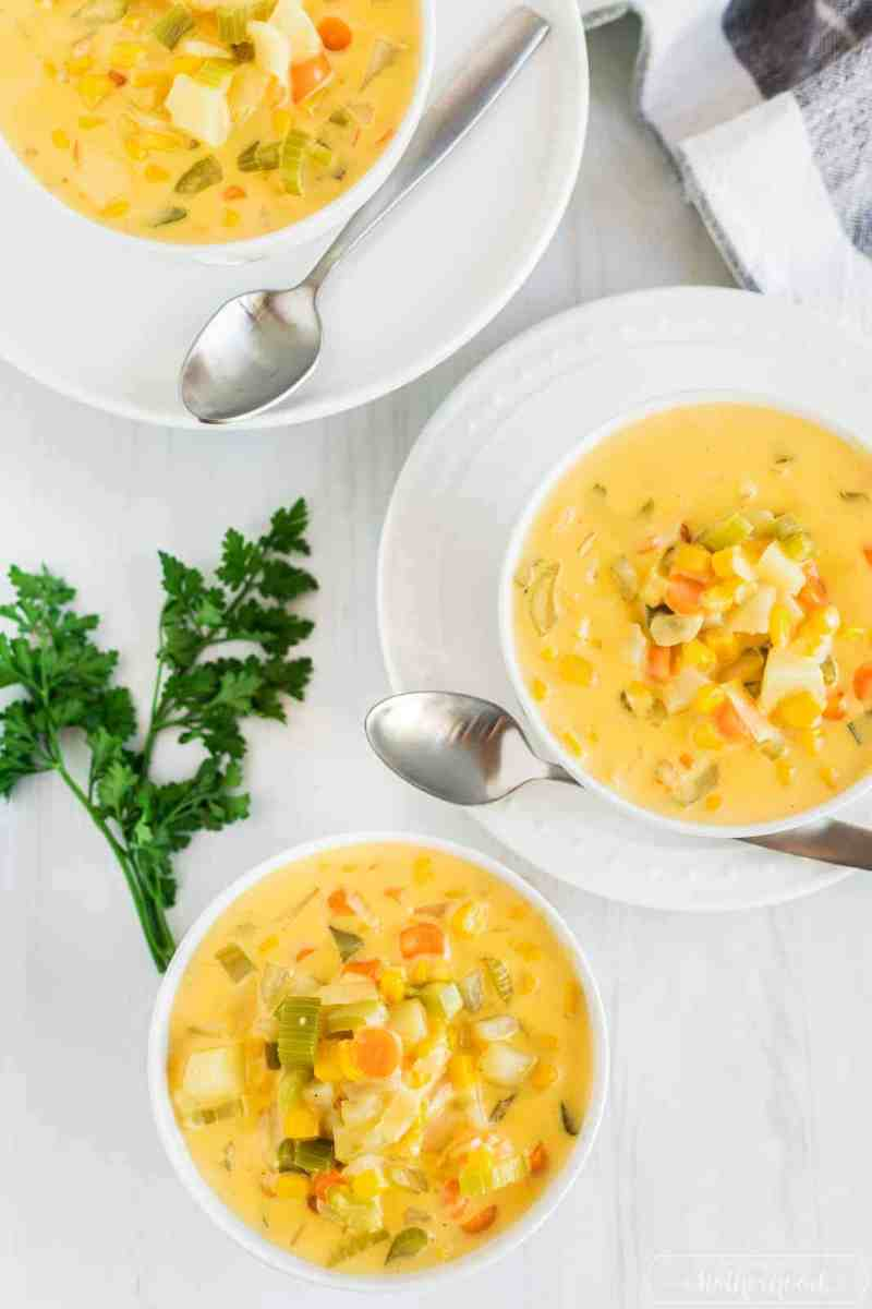 three bowls of delicious corn chowder with a sprig of parsley