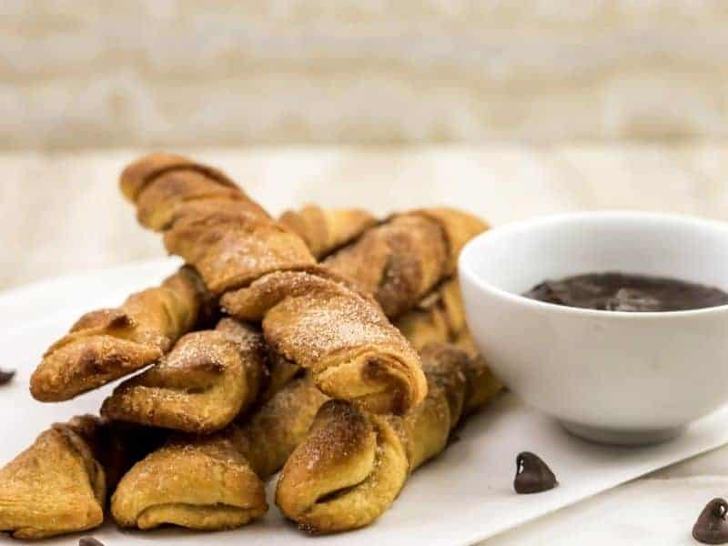 baked churros on table with chocolate dipping cause