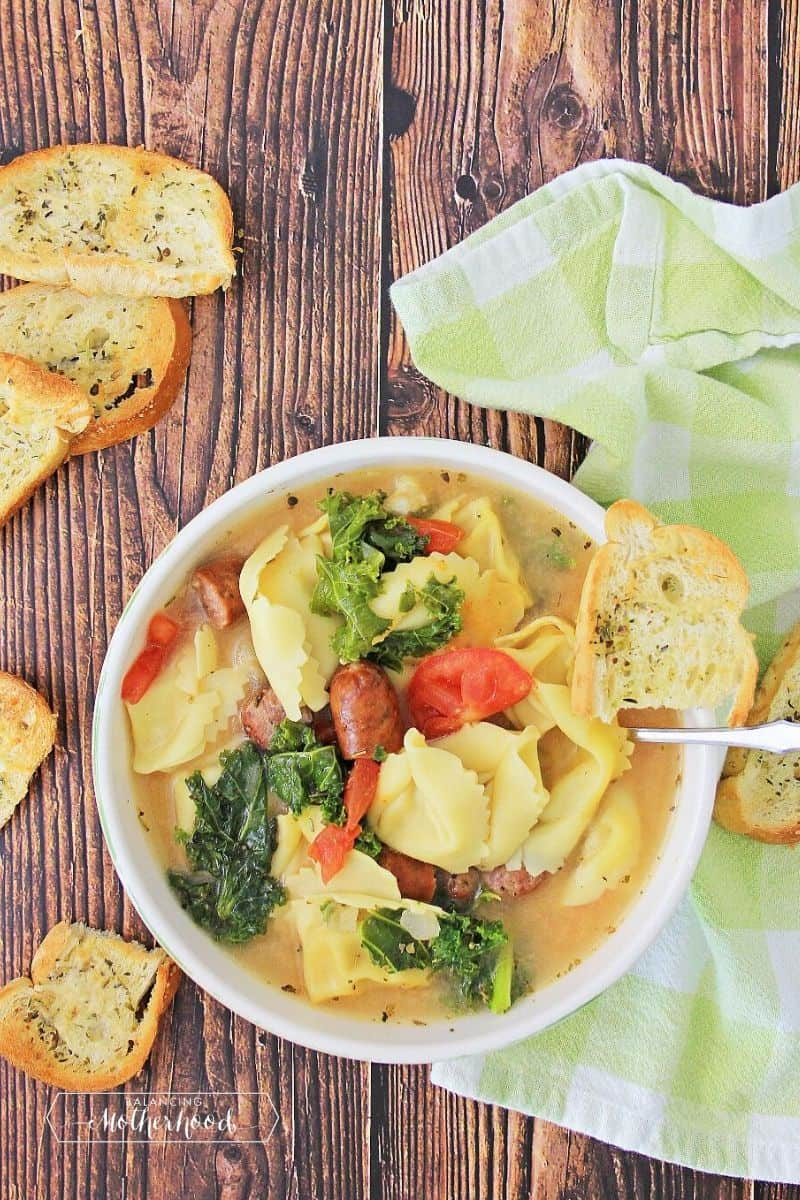 tortellini soup with bread crisps on wood board with kitchen towel