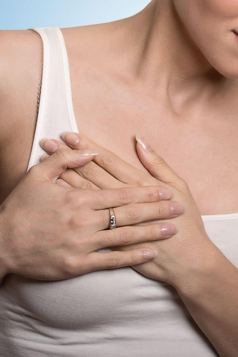 woman clutching breast in pain while wearing a tank top