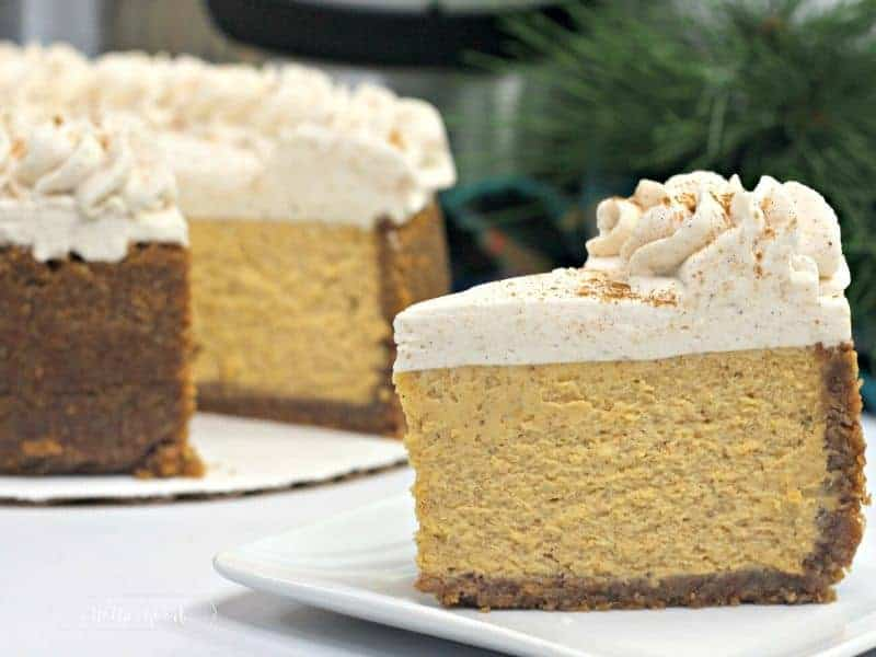 slice of pumpkin cheesecake with whole pumpkin cheesecake in background
