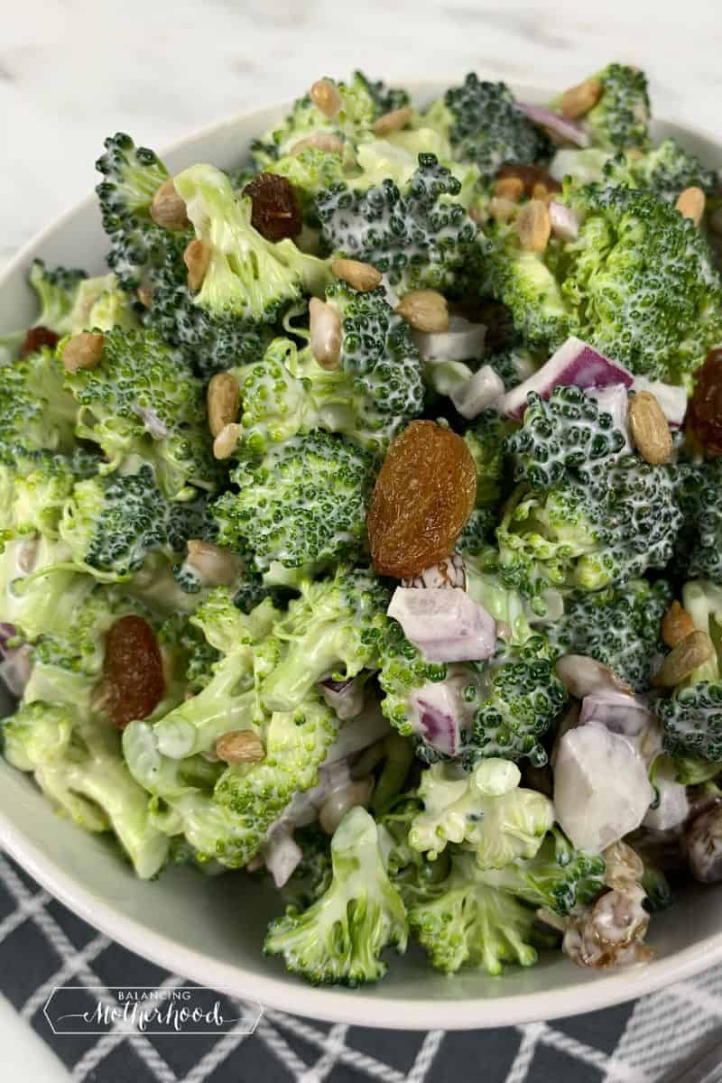 large bowl of broccoli salad on linen napkin