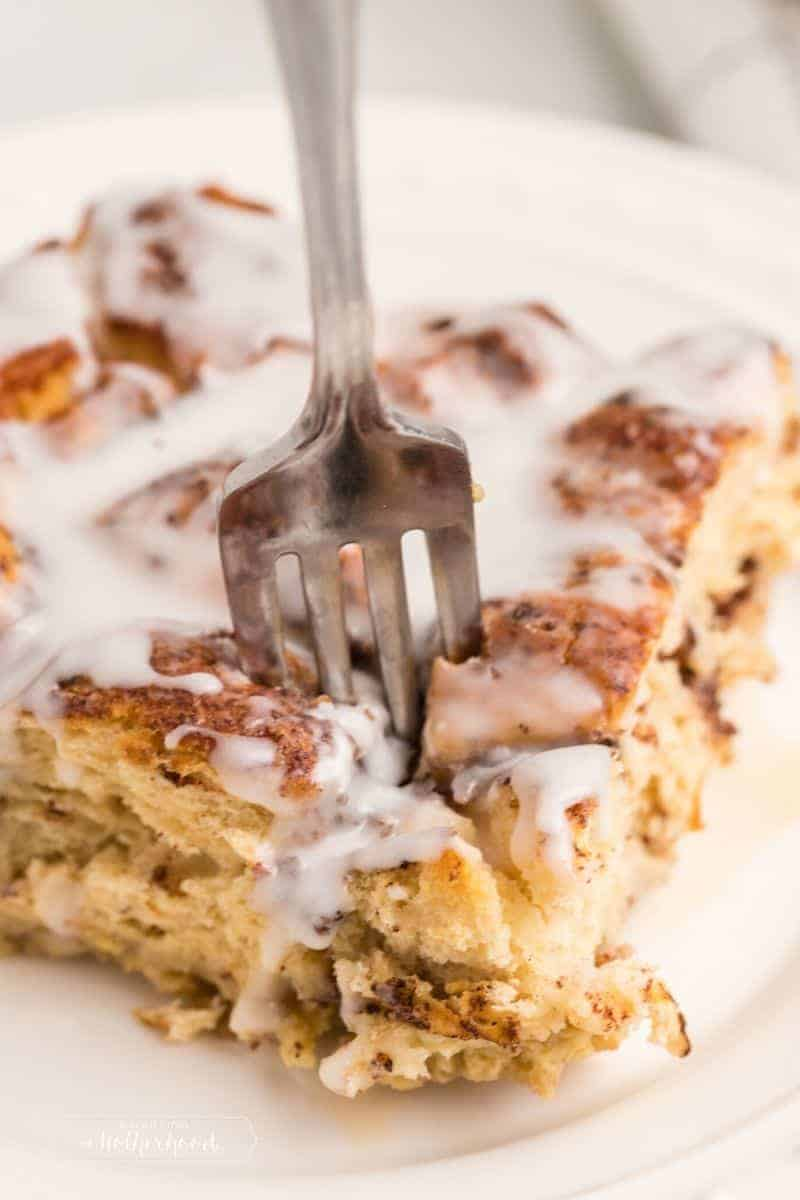 fork taking a bite out of cinnamon roll french toast slice
