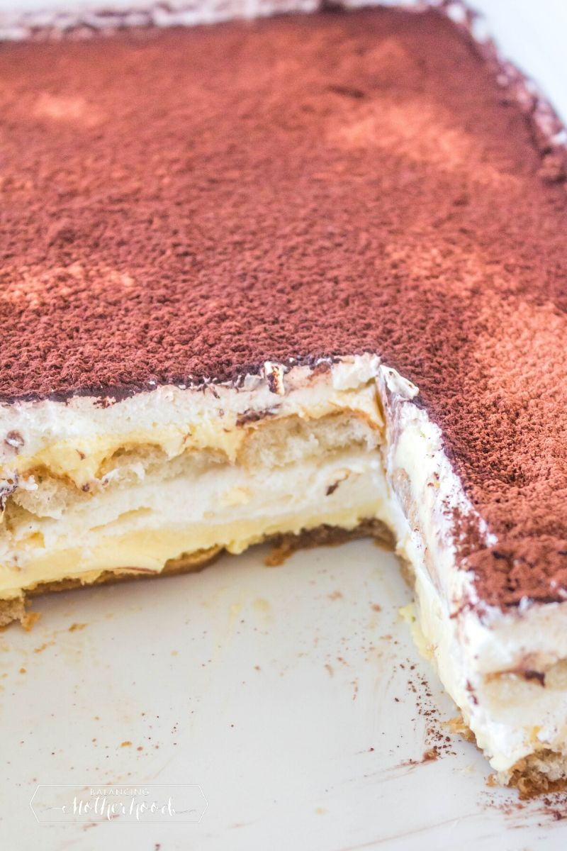 pan of tiramisu with dark cocoa on top layer, you can see the inside layers of ladyfingers and custard